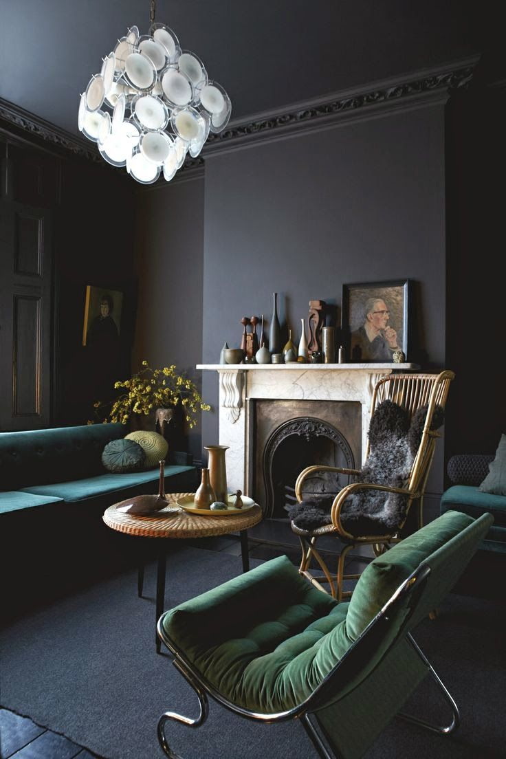 Like the dark walls, the green colour theme for couch and chairs, pillows and the way the mantle area is decorated.