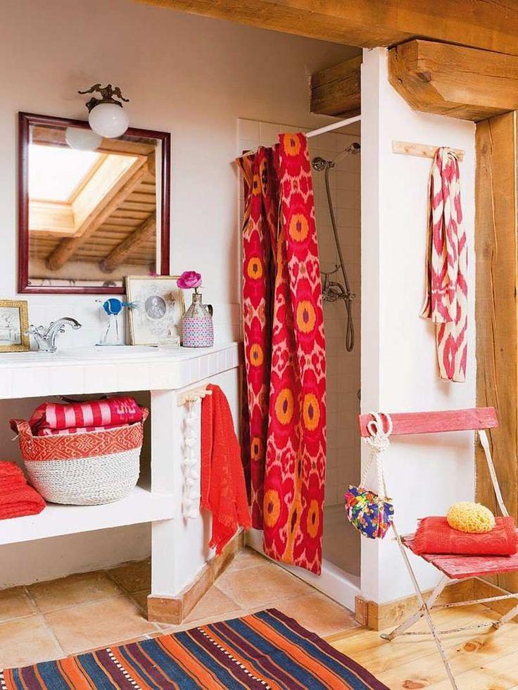 décoration maison de campagne - salle de bains blanche avec une cabine de douche carrelée, rideau de douche rouge à motifs orange et un tapis rustique rayé