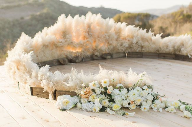 pampas grass decor Our team at Christine Cater created the ceremony space around a hand-painted aisle runner using ombre flowers in whites, pinks and plums that ended in a circular pampas grass altar surrounded by ghost chairs.