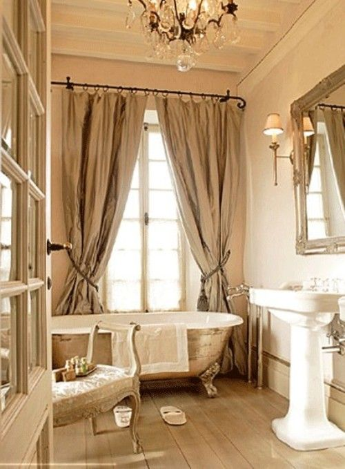 Champagne colored curtains and French accents make this bathroom feel decidedly French. A crystal chandelier sparkles above a soaking tub. What other light fixture could we expect in such a lovely bath?    ~frenchmadame