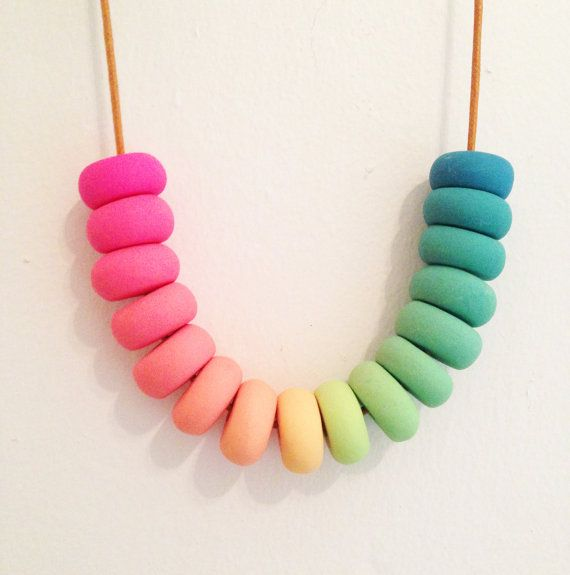 Polymer clay bead necklace (16 disc beads each with a 2cm diameter). Hand blended and rolled beads. Round leather cord. Two slip knots -