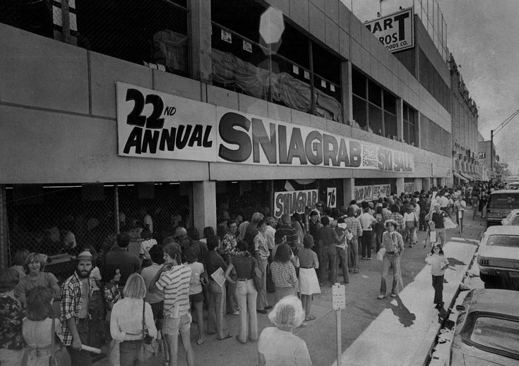 ". Prospective buyers crowd the sidewalks along Broadway, waiting their turn to shop at the 22nd annual ""Sniagrab\"" ski sale in 1976 staged by Gart Bros. Sporting Goods Co. The sale, which gets its title from the word bargains spelled  backwards, is housed this year in a new addition  to the main Gart store, 1000 Broadway. Credit: Denver Post"