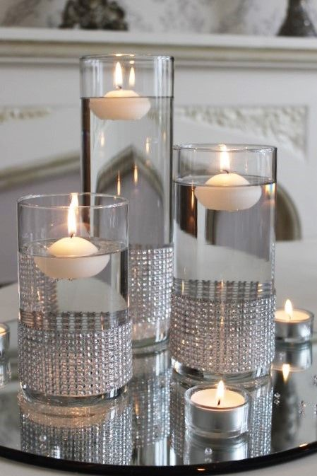 Set of cylinder vases with diamante bands and placed on a mirror plate and silver sequin table runner would create a cheap and easy to set up table centrepiece.