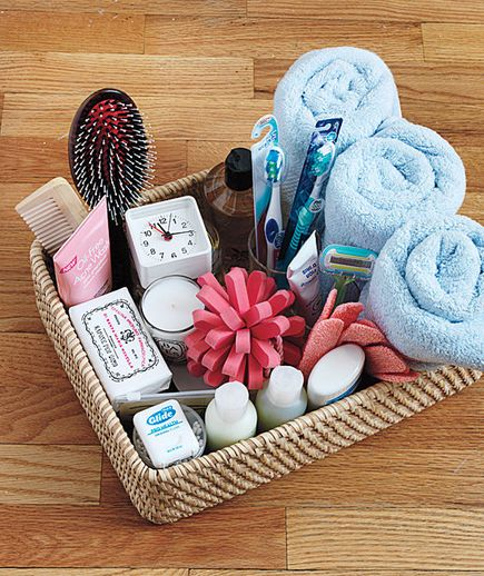 Hospitality basket of bathroom items. A supply of just-in-case items for overnight guests, including a scented candle and an alarm clock.: