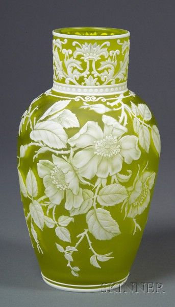 Webb Cameo Glass Floral and insect decorated vase, Stourbridge, England.  White cameo cut on citron-colored body, decorated at neck with leaves between white bands, the body decorated with open petal, roses, buds, leaves, and stems, the opposite side with two moths and a palm frond, double white band at base, stamped Thomas Webb & Sons/Gem Cameo on base, ht. 9 in.  Sold at auction for $ 8,000.