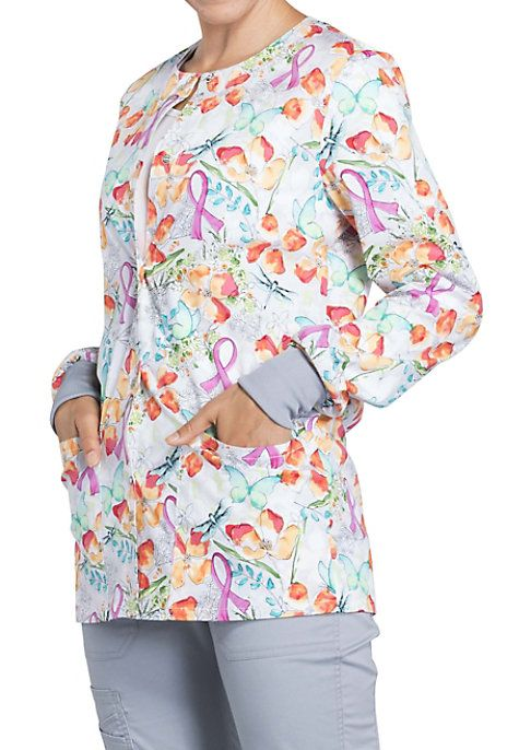 The Springtime Love Scrub Jacket is the perfect way to keep warm this season. The lovely print features flowers in various colors and pink ribbons to show your support for Breast Cancer Awareness. The comfy stretch fabric gives you full range of movement. Two patch pockets make this jacket functional as well. Cherokee Springtime Love Breast Cancer Awareness Print Scrub Jackets Round neck Modern fit Snap front Two patch pockets and an instrument loop Back yoke Knit cuffs 97% cot...