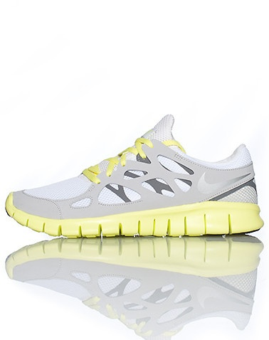 NIKE Low top women's running sneaker Lace up closure Mesh throughout Flexible material for ultimate comfort Cushioned sole Grey shoe with yellow accents $70