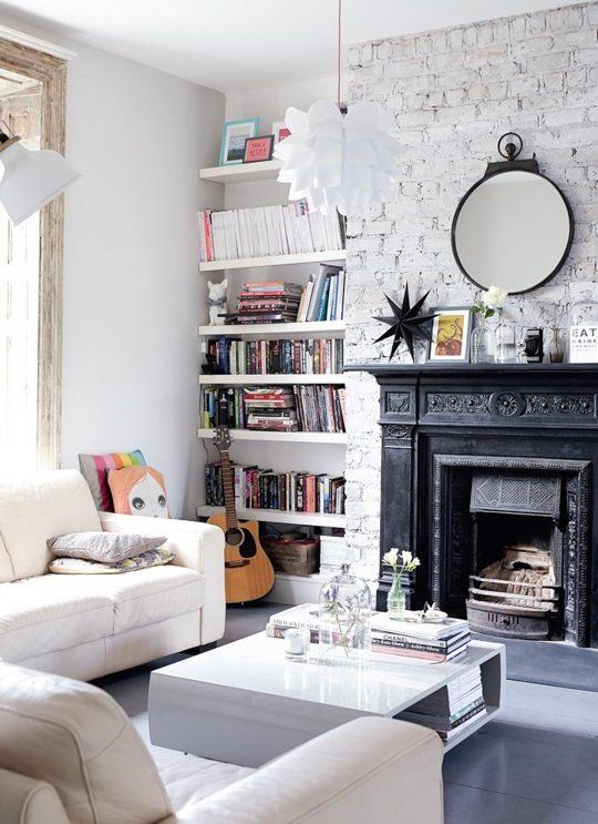 A bright white living room with modern furniture, a white painted brick wall and a black ornate architectural fireplace.