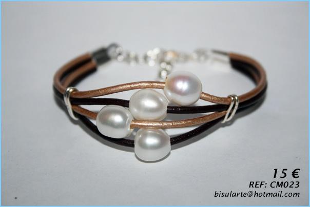 Pulsera de cuero en marrón y dorado con perlas cultivadas y cierre de mosquetón. Puedes combinarla con el anillo y la gargantilla a juego.