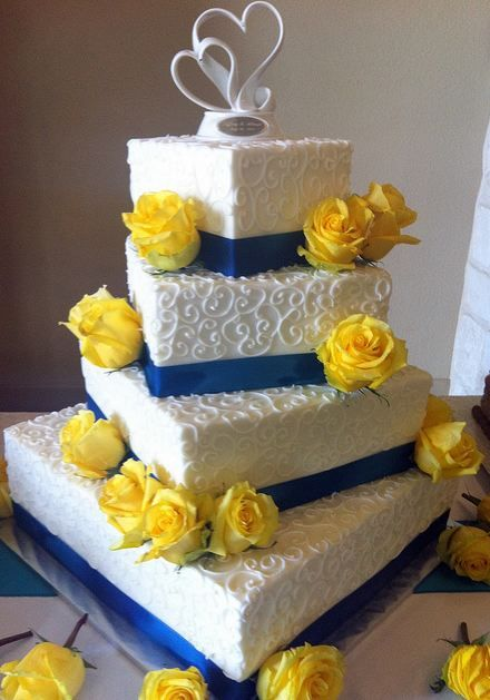 Four tier white offset rectangular wedding cake with blue bands and yellow roses.