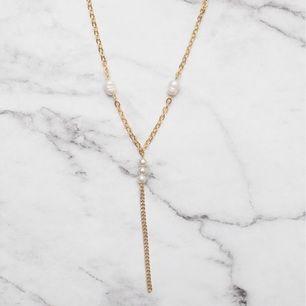 Unikt guldfärgat halsband med vita pärlor. Justerbar kedja. 7:- i frakt tillkommer.