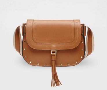 This saddle bag is made of leather. Medium in size, it is finished with stitching, studs and strap fastening for the flap. The adjustable shoulder strap combines ribbon and leather.  Product name:SEGNAVIA Product code:5511086003001  See more Accessories