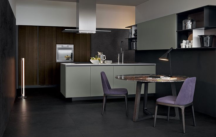 Varenna_Alea kitchen with creta embossed lacquered base units, worktop in superwhite micro-blasted quartzite. Tall units in spessart oak. Wall mounted shelves Skip in nero mat lacquer, nero and bianco mat lacquered partitions, creta mat lacquered doors. Island-hood in steel. Concorde table in spessart oak with emperador dark marble table top. Grace chairs in spessart oak and fabric.