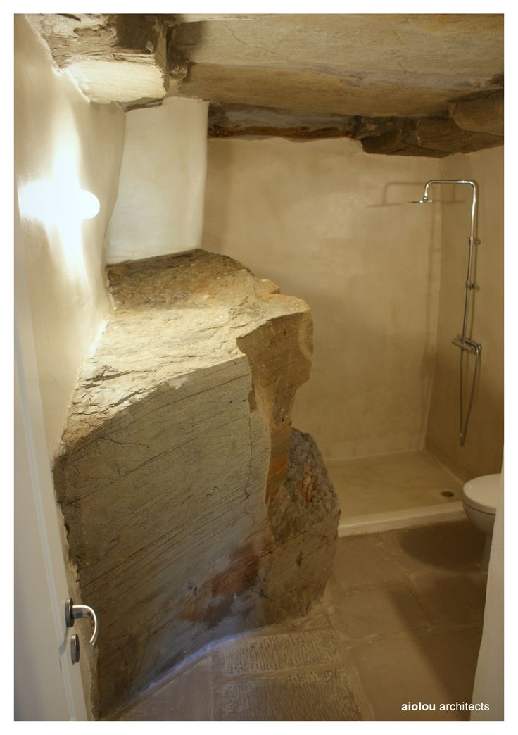Bathroom built into the natural bedrock with a micro cement wall finish and stone floor. www.aiolou-architects.com #andros #renovation #bathroom