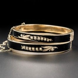 A matched pair of Victorian bangle bracelets, lovingly rendered in 10 karat gold, each inlaid with glossy black enamel adorned with golden seed-pearl studded Lily-of-the-Valley motifs. Beautifully hand-engraved at the hinge and clasp. Circa 1885, they fit a small wrist size.