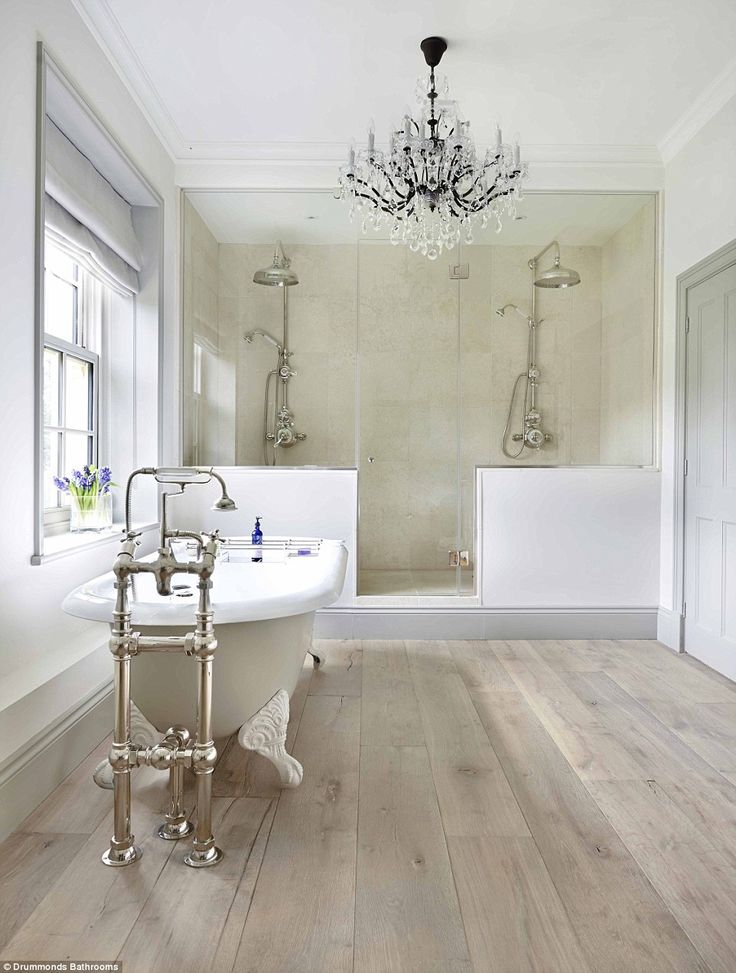 This glamorous bathroom in a Georgian farmhouse in Surrey was designed by Milly Goodwin and features a black-framed crystal chandelier above a freestanding bathtub