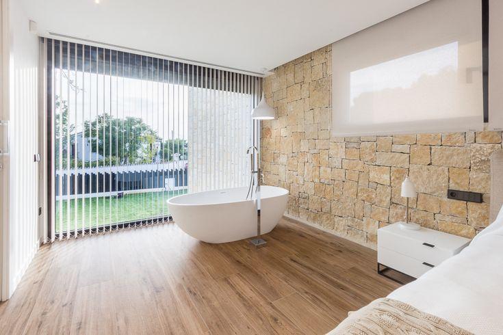 Dormitorio con bañera integrada y vistas al jardín en tonos claros en casa de diseño Cumbres | Chiralt Arquitectos Valencia