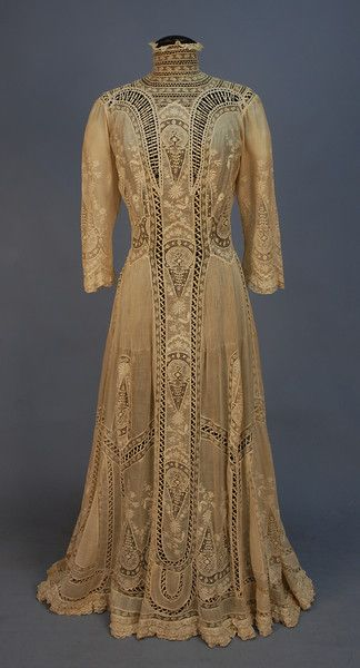 LACE HIGH NECK TEA GOWN,   1900's.   White cotton batiste 1-piece lavishly decorated with tucks, embroidery, and various laces, elbow length sleeve, shell buttons at back. B-34, W-24, L-57.