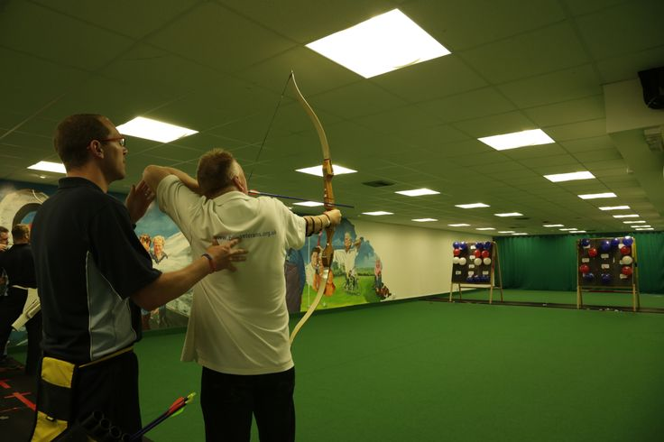 Craig is helping Blind veteran Colin Williamson line up his shot in a fun archery competition between Blind Veterans UK and the US Blinded Veterans Association. Photo credit: blind veteran Chris Nowell