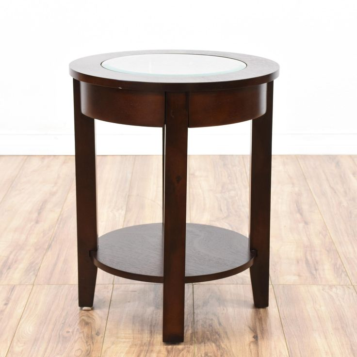this end table is featured in a solid wood with a glossy dark cherry finish this side table has a round glass table top a bottom shelf tier