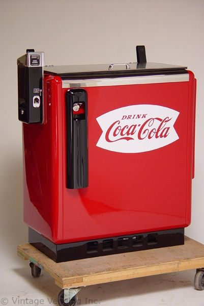 coca-cola machine - put money in top/side, lift top, grab the soda by the top/cap, slide your drink to the opening and lift up.