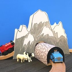 Make a mountain and tunnel to go along with wooden train tracks with things you probably already have around your house.