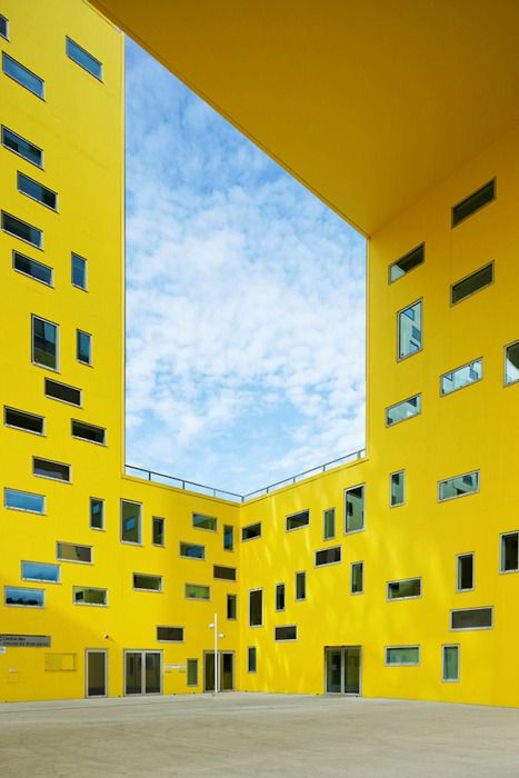 Empty atrium surrounded by yellow walls and above: open white cloudy sky with intermittent light blue