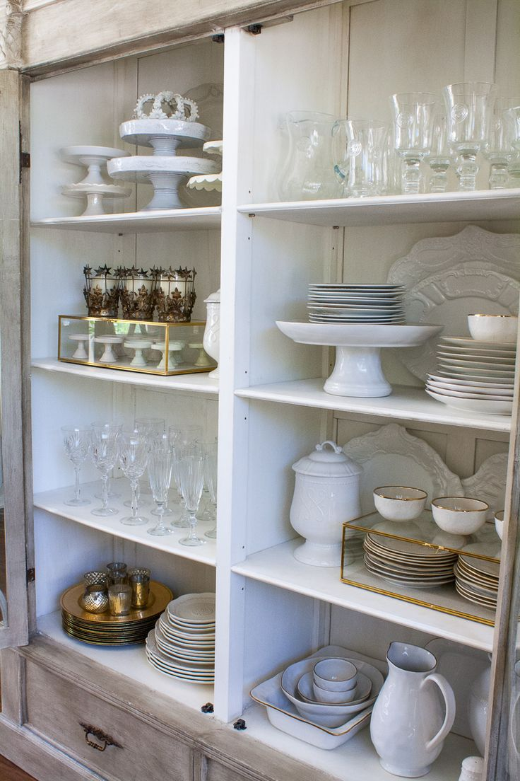 How to style your china cabinet. China Cabinet Essentials  A set of white dishes {dinner plates, salad plates, bowls} Set of glassware {stemware & tumbler} Set of Silverware {gold and / or silver} Napkin Rings Chargers 3-5 Serving Platters Large Pitcher Cake Plates Votives & Candle Sticks White Napkins
