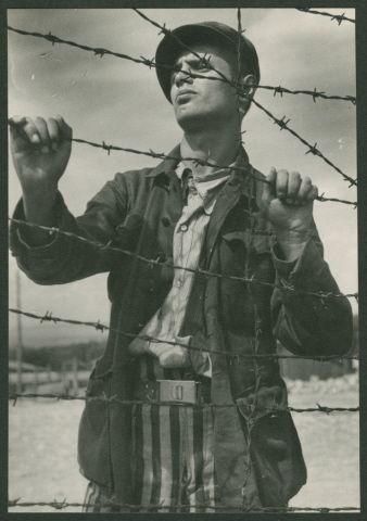 A survivor stands next to the barbed wire fence of the Buchenwald concentration camp following liberation.