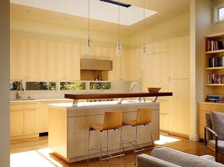 Световое окно в потолке кухни ярко освещает кухонный остров, а отраженный свет освещает и прилегающую гостиную. .