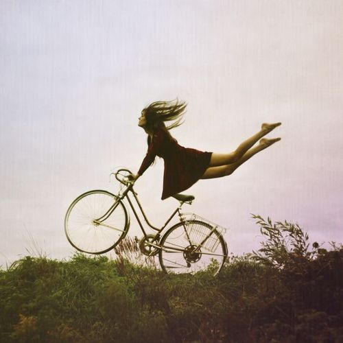 woman riding bicycle,  legs flying back in wind, hanging onto handles bicycle flying