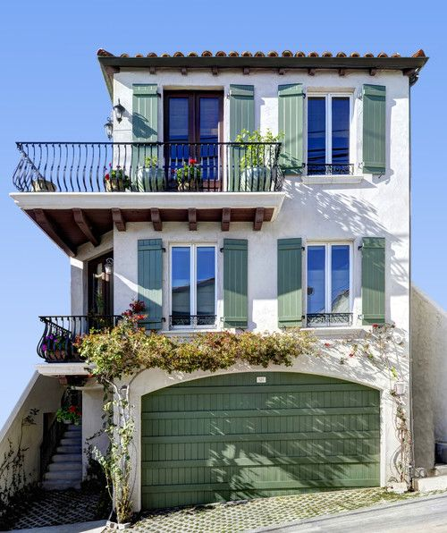 White exterior siding, green shutters and garage, iron deck railings. Moonstone Street residence, Manhattan Beach. Schneider Custom Homes.