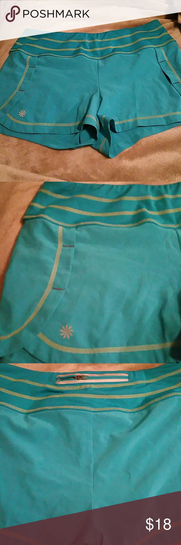 Athleta Small Turquoise Blue Running Shorts Athleta Size Small Turquoise Blue Running Shorts  86% polyester 14% spandex  Wide waist band to prevent muffin top  Cooling type material  Inner lining   Zipper in back to hold key, credit card, etc  Cute side stiching  and smooth corners for unique modern look  Worn once just to try on  I have a dog, but he's kept away from clothes, just a heads up.  Thanks for looking! Athleta Shorts