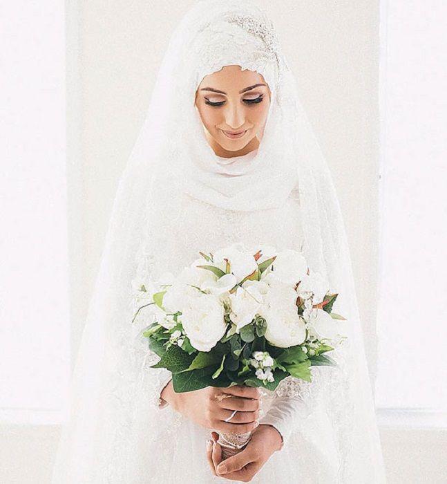 Простой букет из белых роз придает образу невесты невинности.
