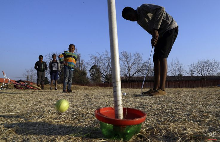 A child plays a shot during a game of golf  at a park in Katlehong township, east of Johannesburg, South Africa, Thursday, July 16, 2015. (AP Photo/Themba Hadebe)