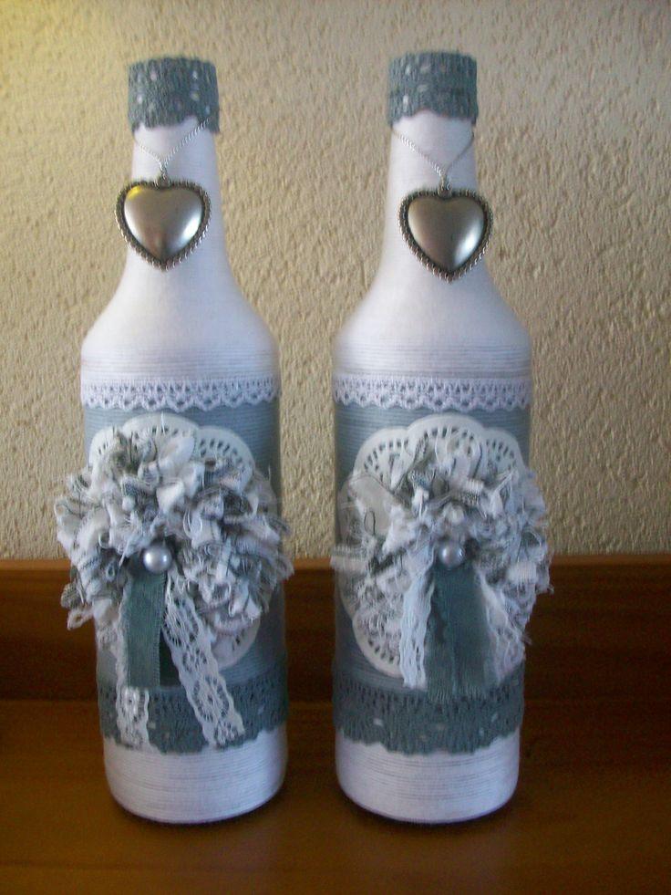 Oude limonadeflessen, omwikkeld met katoendraad ( grijs en wit) , daarna versierd met kant ( grijs en wit) en een zelfgemaakte bloem van linnen en taartrandje.