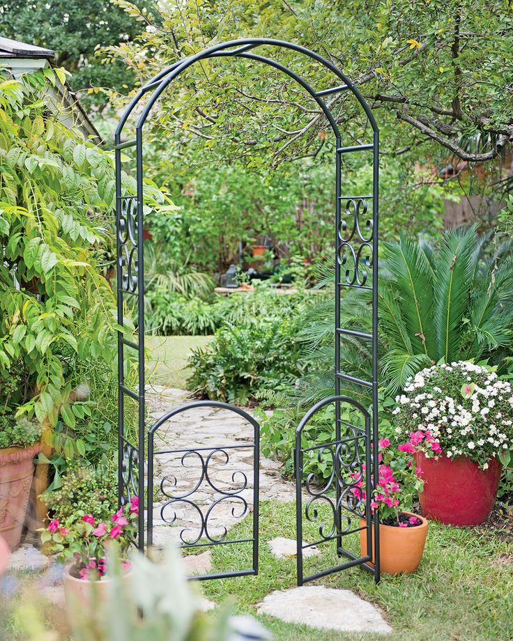 Laurel Garden Arbor with Gate.  Standing almost 7' high with a built-in gate, this arbor is a lovely way to welcome garden visitors. The simple yet elegant outline is punctuated by delicate quatrefoil scrolls, and the rich, matte-black finish resembles wrought iron. Made of powder-coated tubular steel.  Gardeners.com