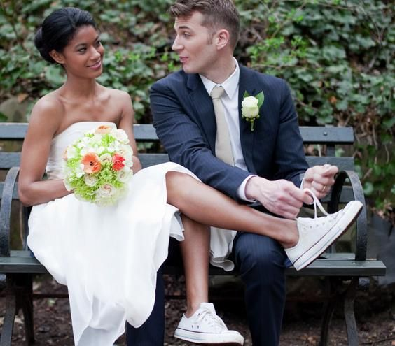 Groom tying bride's sneakers - Landscape | Getting hitched on a budget? Never fear—try these 12 tips to cut your costs.
