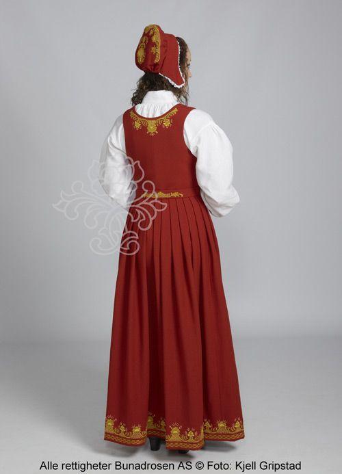 Rød Romeriksbunad L40 med lue og stoffbelte med broderi. Hovudplagg: Høglue med ein stor brodert pull eller ei hettelue med broderi.