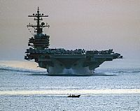 A small fishing boat transits in front of the #USNavy aircraft carrier USS George H.W. Bush in the Strait of Hormuz.