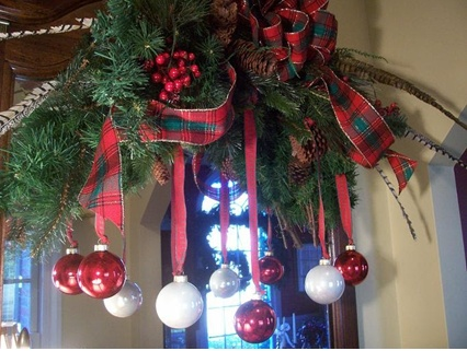 Over the door Christmas bough with ornaments on ribbon.