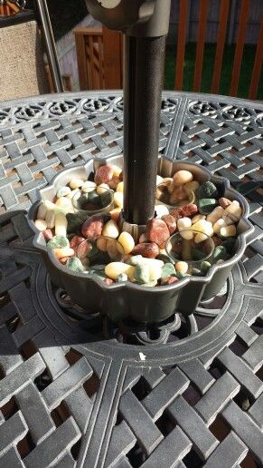 Bundt pan as the centerpiece on the patio table. The umbrella through the center,  holes drilled at the bottom of the pan for water drainage.  Filled with river rocks and candles.