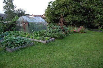 V okolí ksleníku jsou sdruženy záhony se zeleninou a ovocné keře. V pozadí je kompost posázený dýněmi a okurkami.