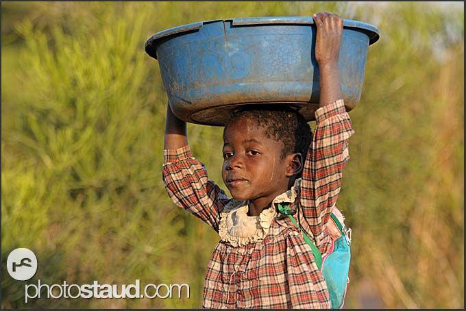 Zambian child carrying laundry on head, Zambia.