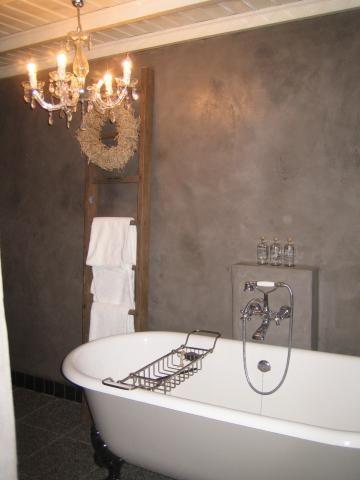 Een prachtige badkamer met kroonluchter en stijlvolle badkuip. De betonnen wand geeft de badkamer een sfeervolle look.