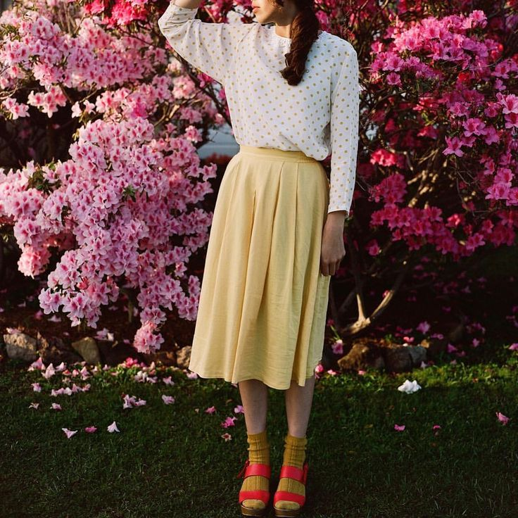 @modestlyrose in thrift: yellow and white polka dot top, yellow pleated skirt, mustard socks, red heels. Image by: @beardeerfox.