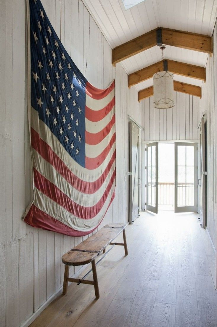 A large old American flag hangs in the hallway of a white painted barn. Photograph from Rachel Halvorson Designs.  |  Design Sleuth: Made-in-the-USA American Flags: Remodelista