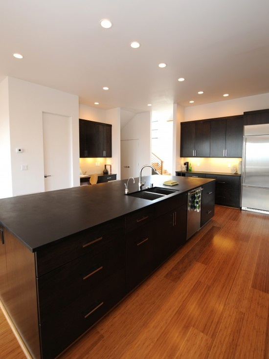 Fabulous kitchen!  The warm tones in the Bamboo flooring help even out the starkness of the black modern cabinets.