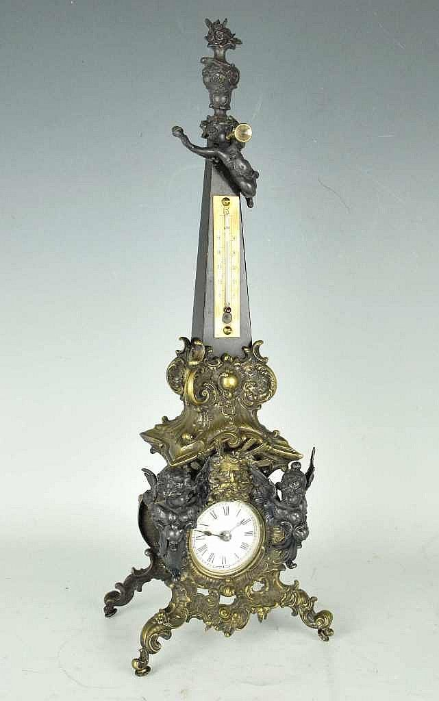 (A) Obelisk form clock with thermometer. Metal base with foliate and angel decoration. Black marble obelisk stem surmounted by an angel with horn having a floral finial...