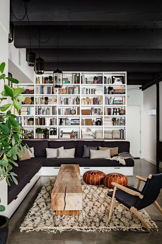 Modern bohemian living space - solid timber coffee table, shag rug, floor to ceiling shelving, comfy lounge, leafy indoor plant & Moroccan poufs.